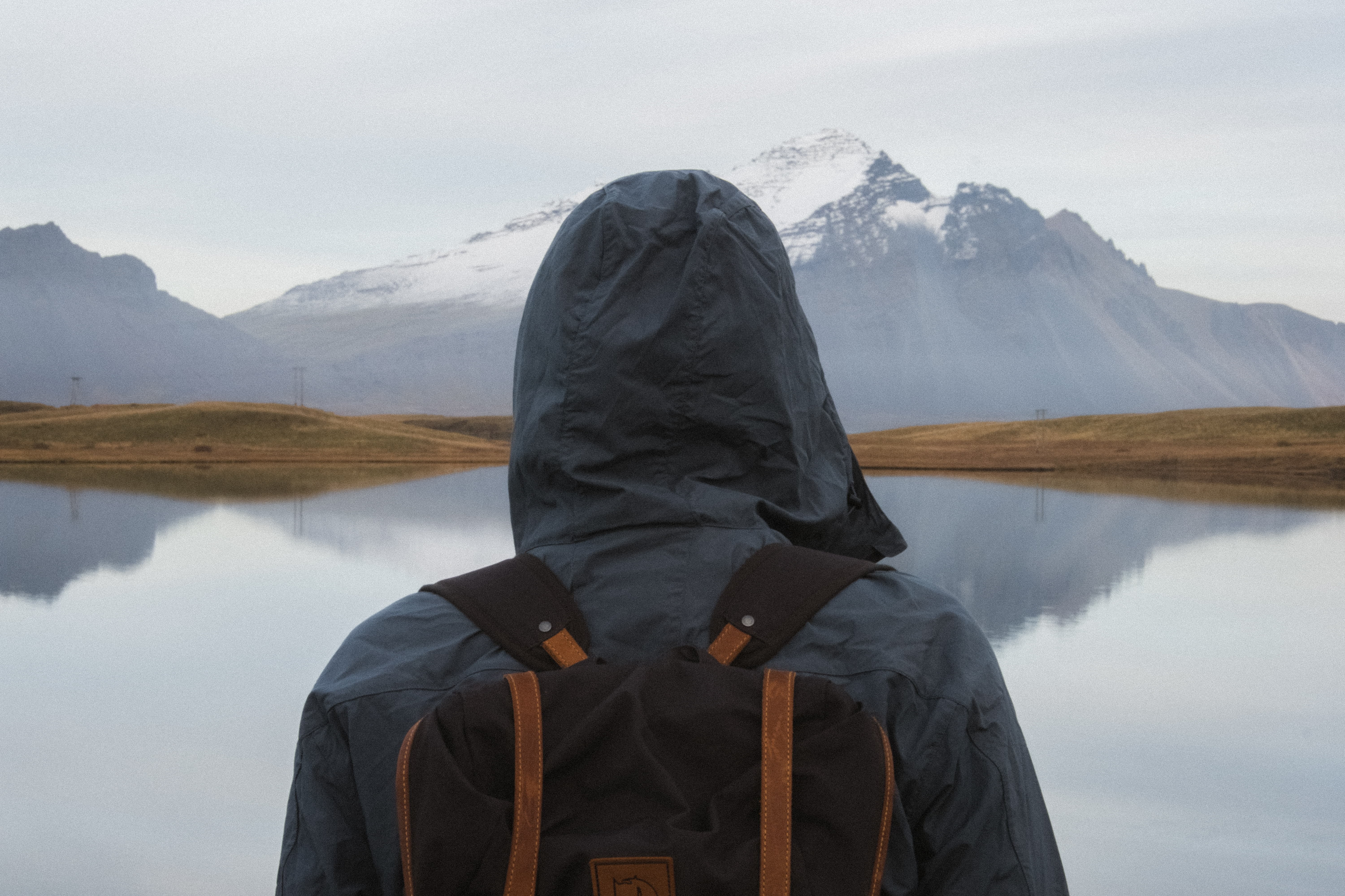 person with backpack standing near body of water during daytime