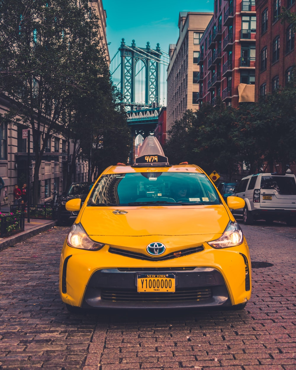 yellow Toyota taxi cab parked near building