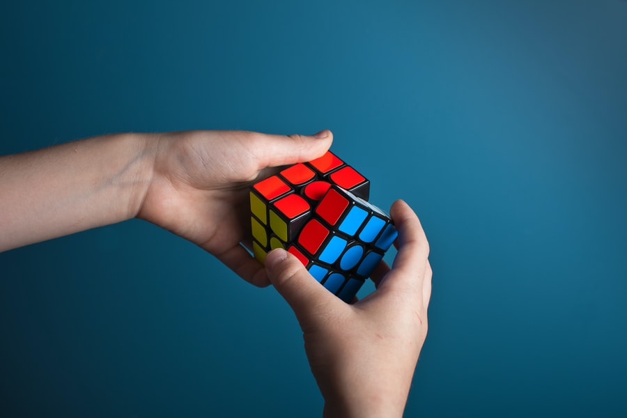 Two hands holding a Rubik's Cube that is mostly solved.