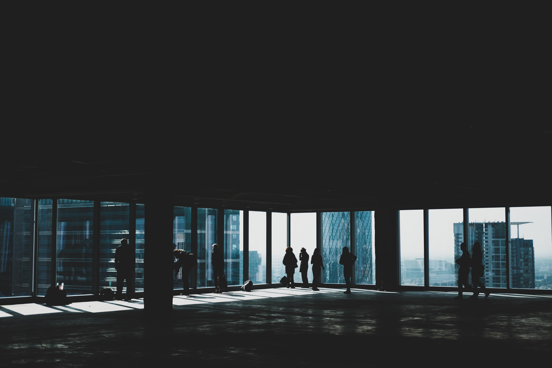 people walking near glass window inside building