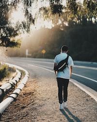 man walking beside road during orange sunset