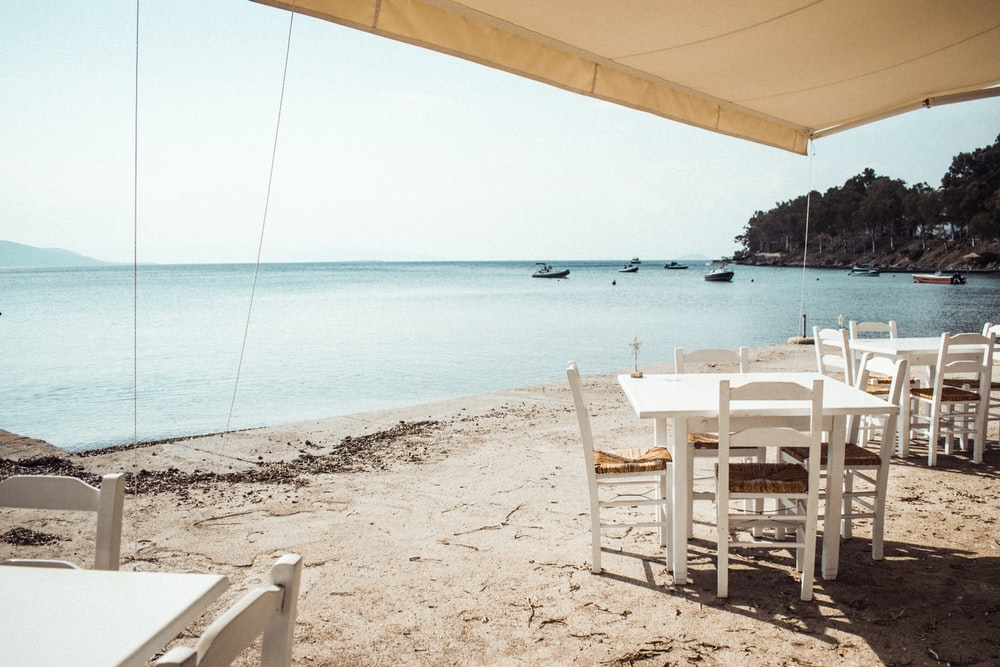 two square white wooden tables and chairs near beach