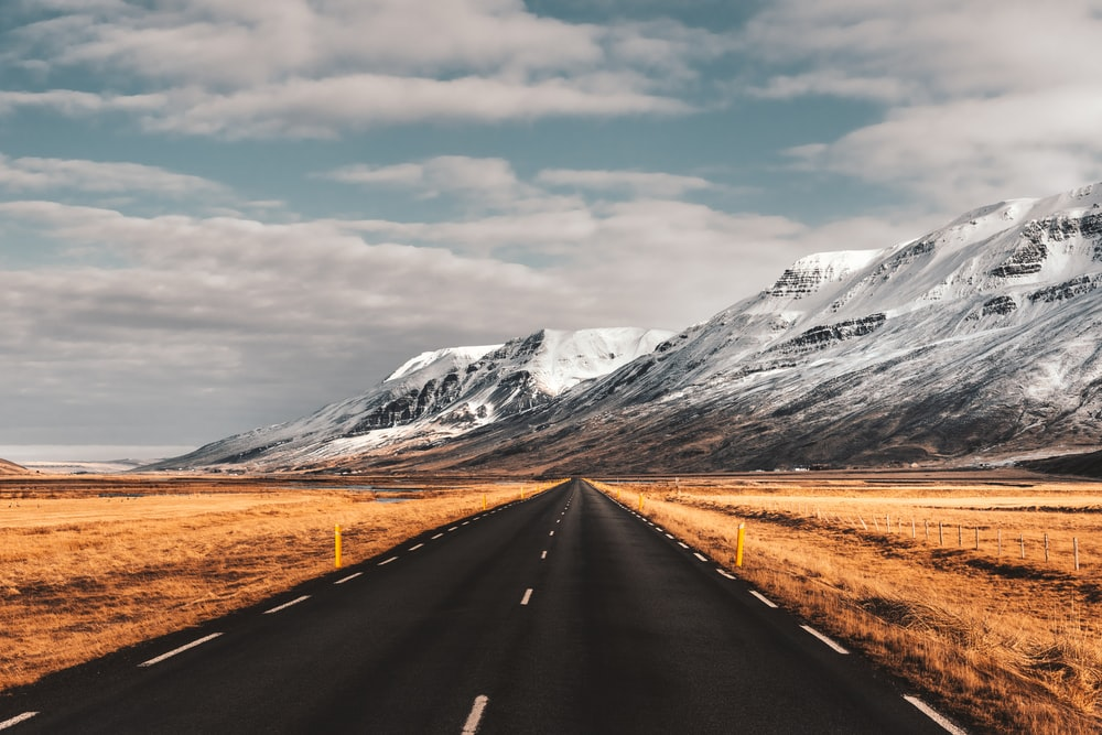 black concrete road towards snow capped mountain under white and blue sky