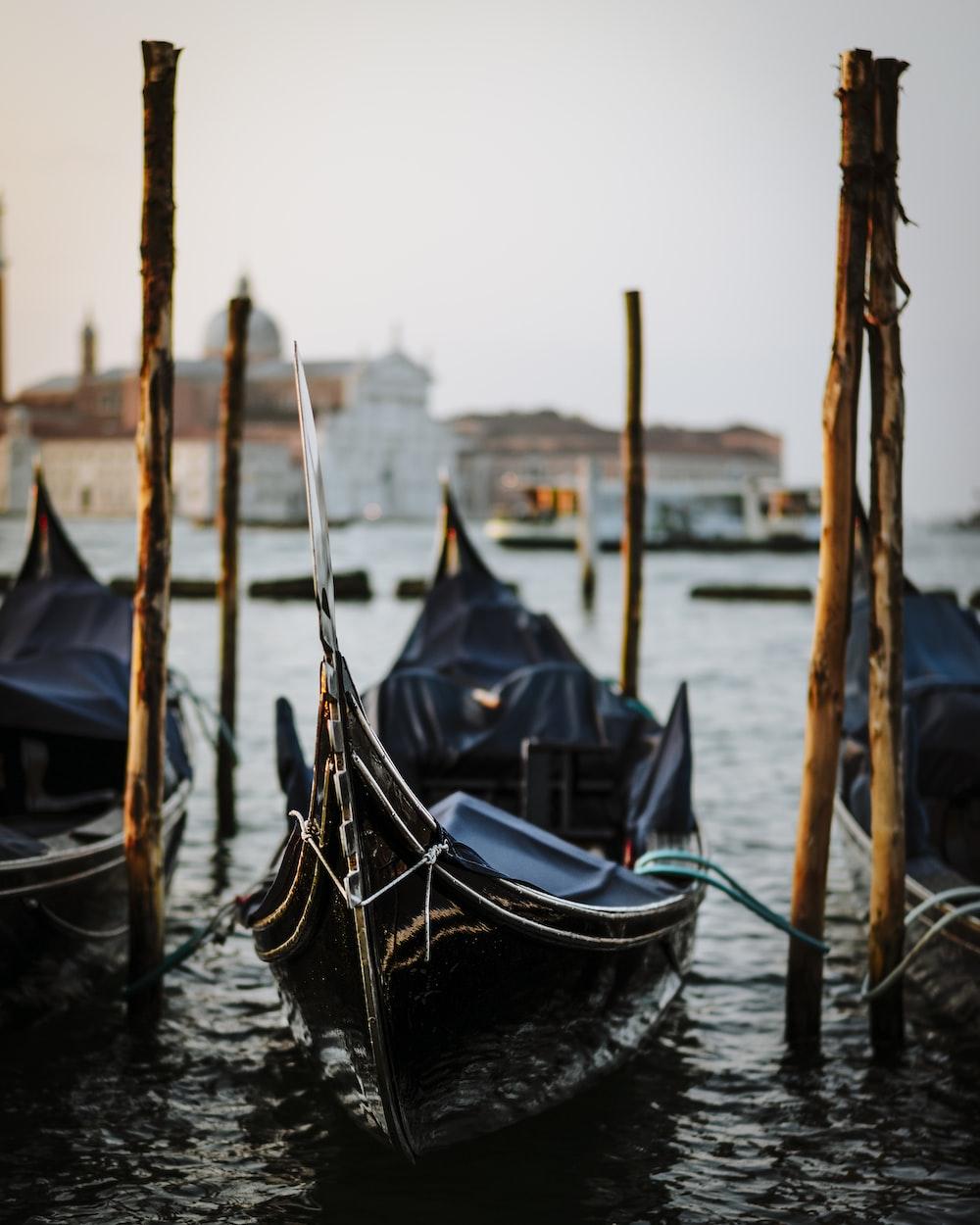 black boat in body of water near poles
