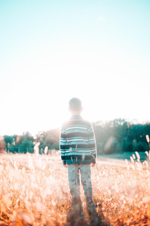 boy in striped shirt standing on grassy field