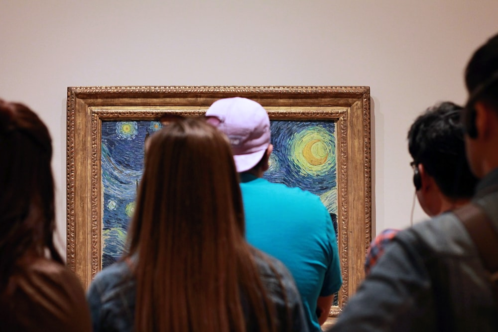 people looking on Starry Starry Night painting with brown frame