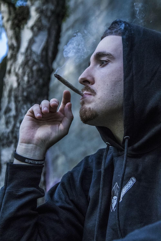 man in black hoodie using brown joint
