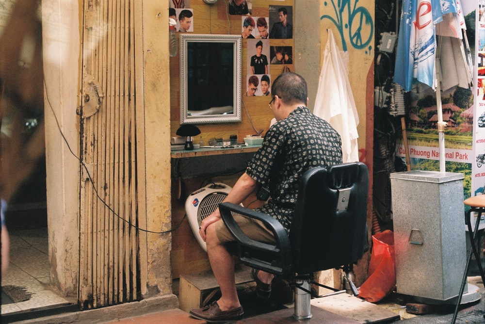 man sitting on barber chair