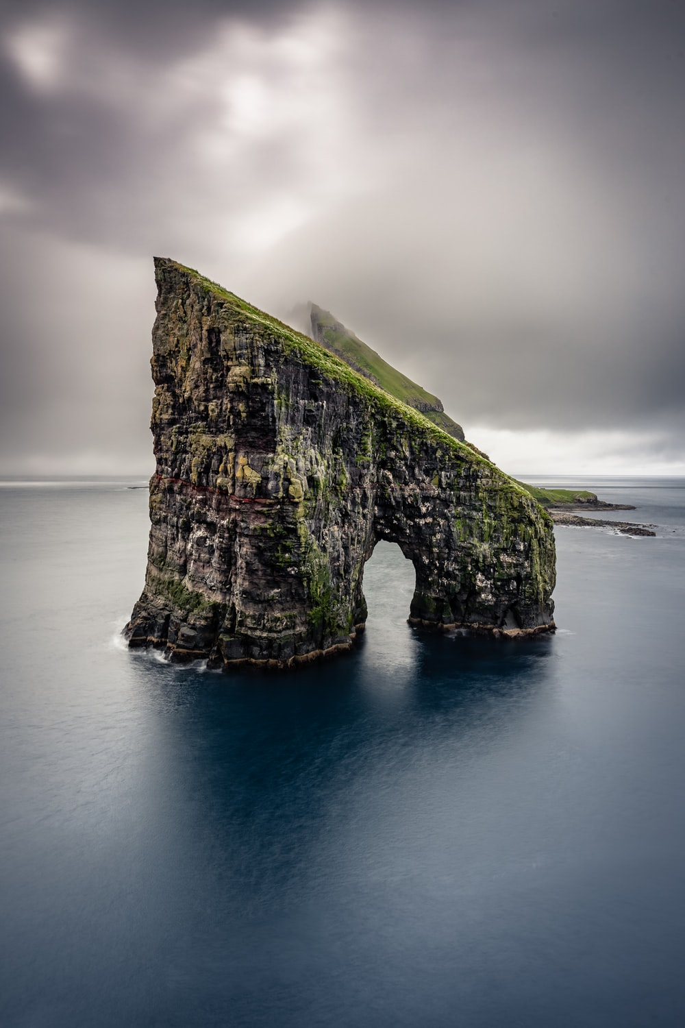 grey and green islet during cloudy day