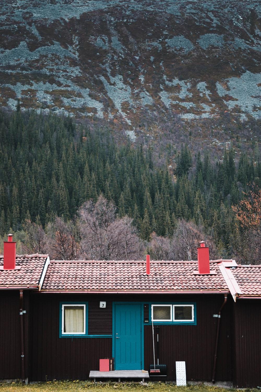 brown wooden house near rocky mountain