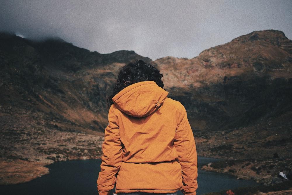 man standing front of lake at daytime