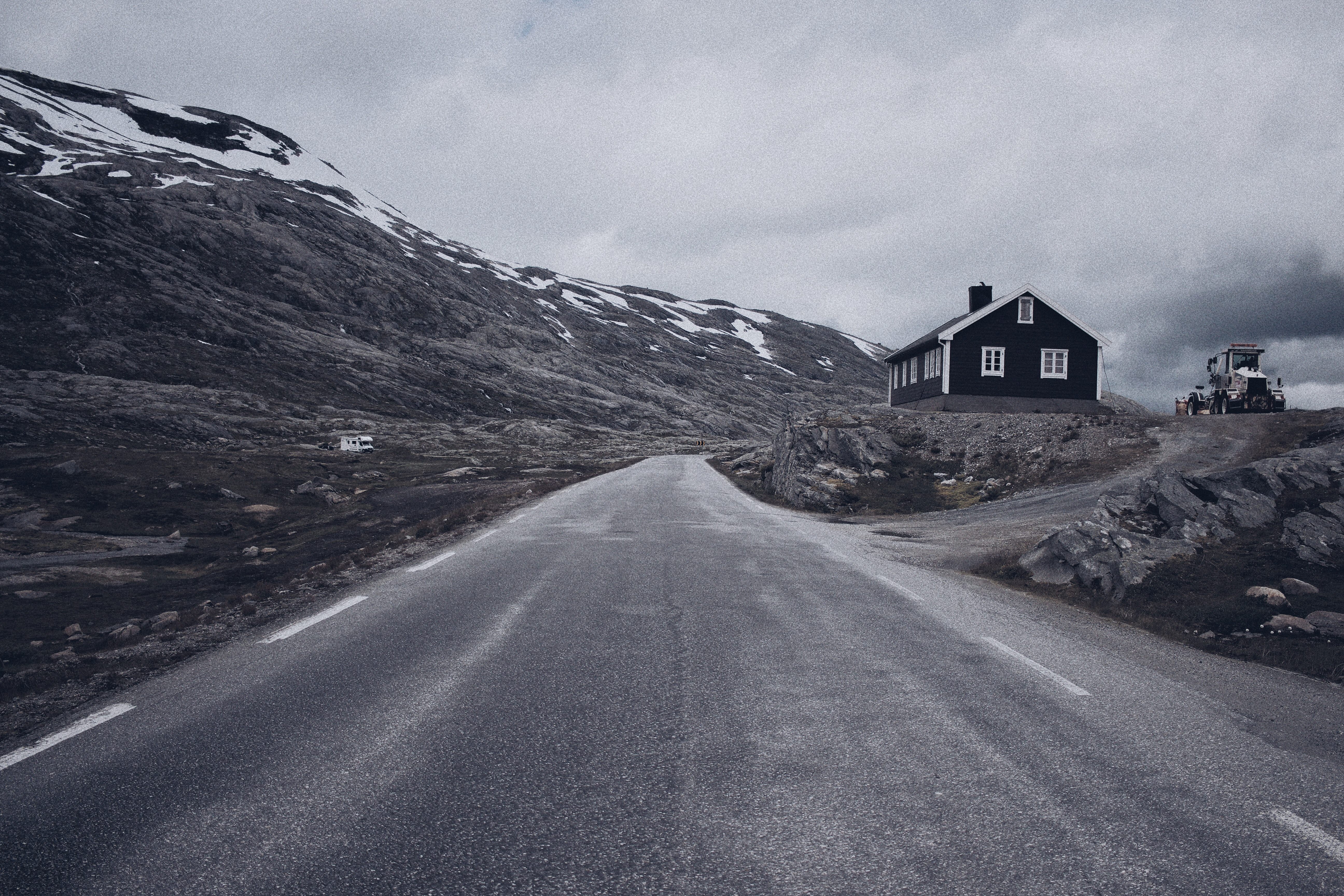 grayscale photo of road beside house