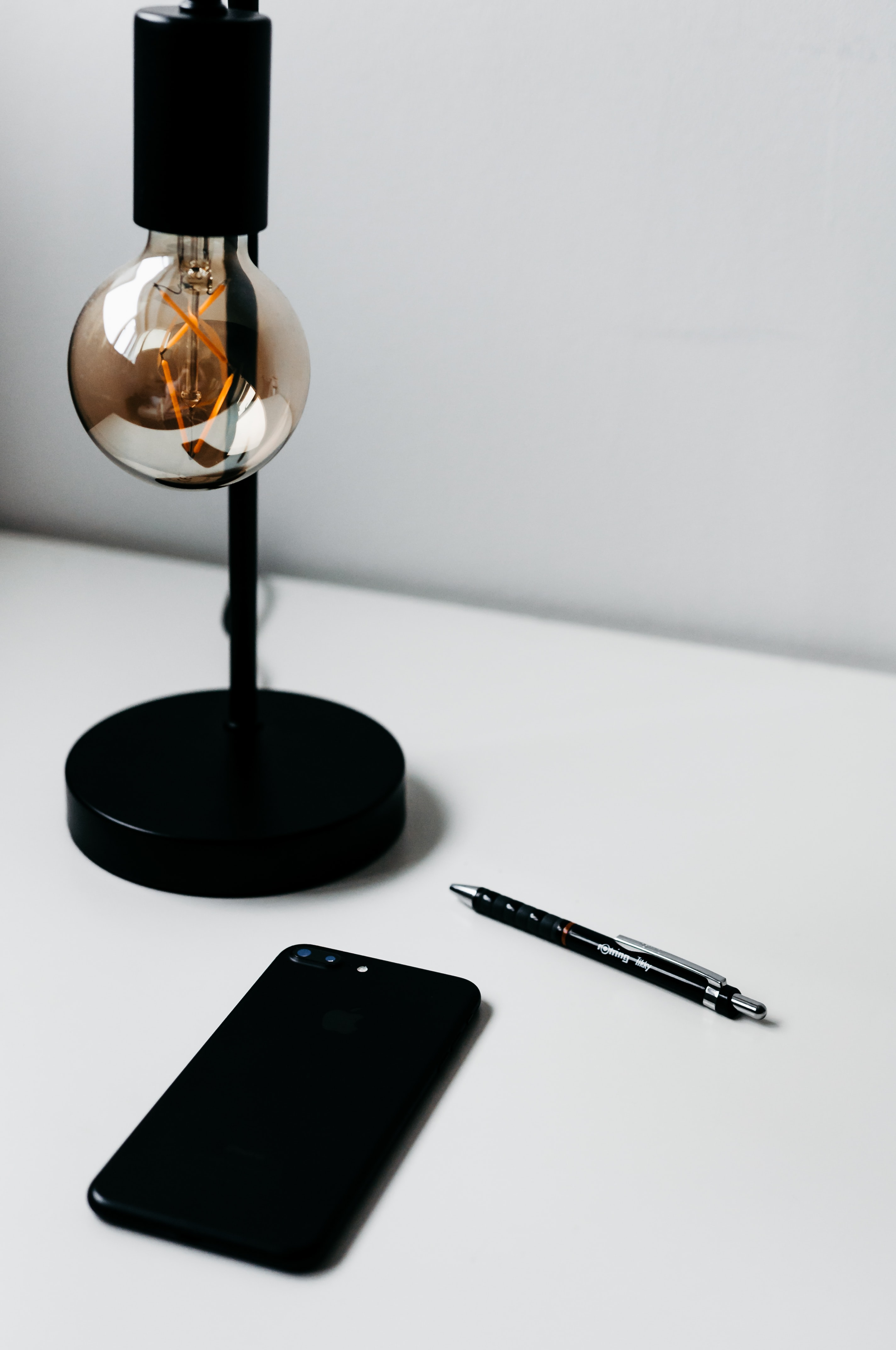 smartphone beside click pen and lamp