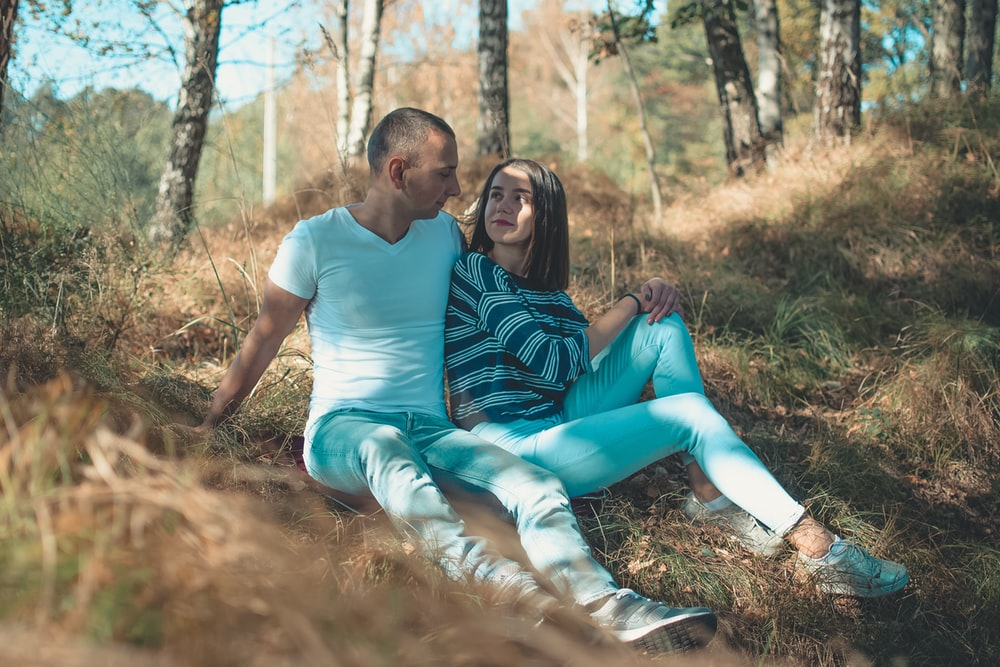 couple sitting on ground near tall trees
