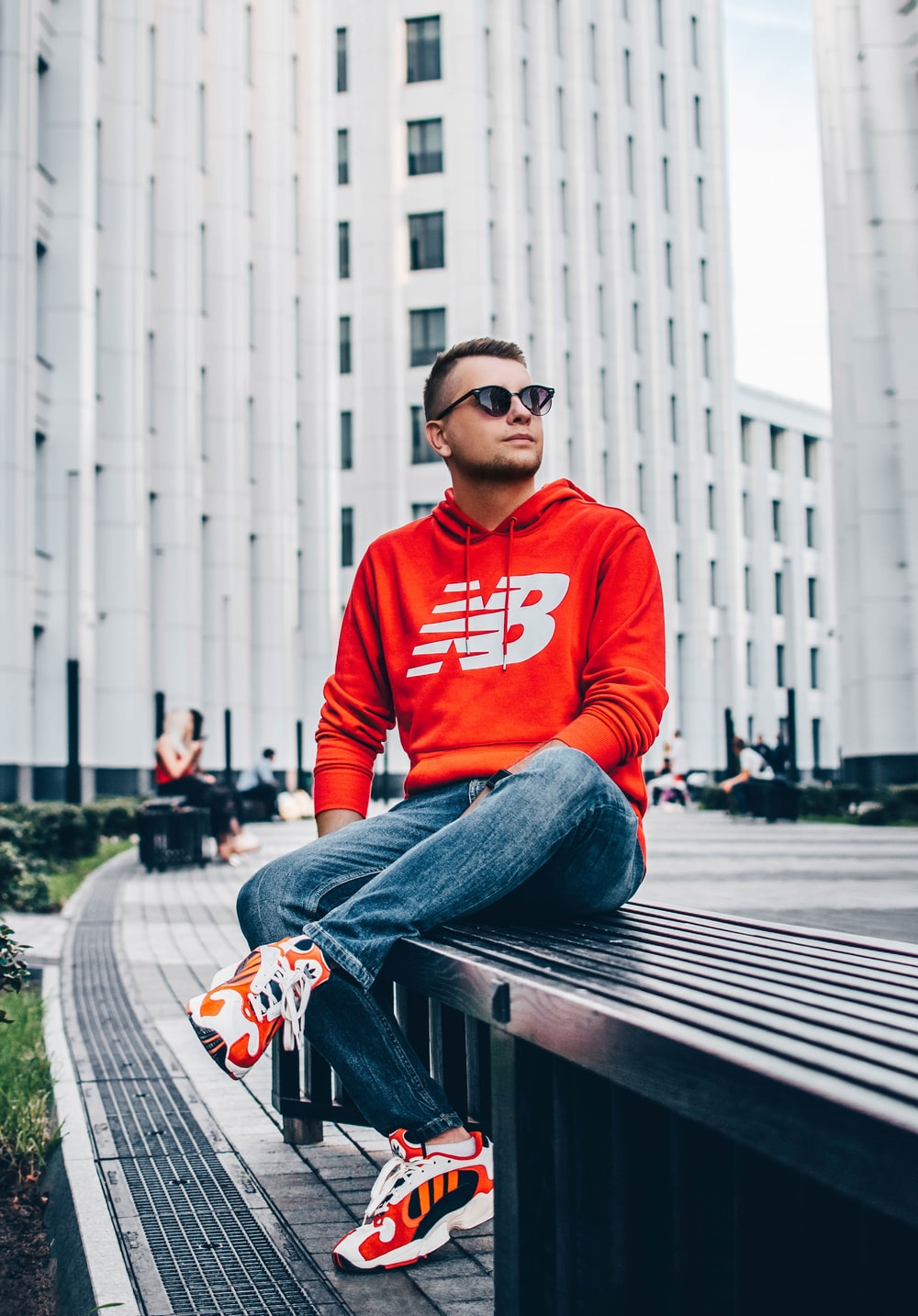 man wearing red New Balance pullover hoodie sitting on black bench in front of white high-rise building
