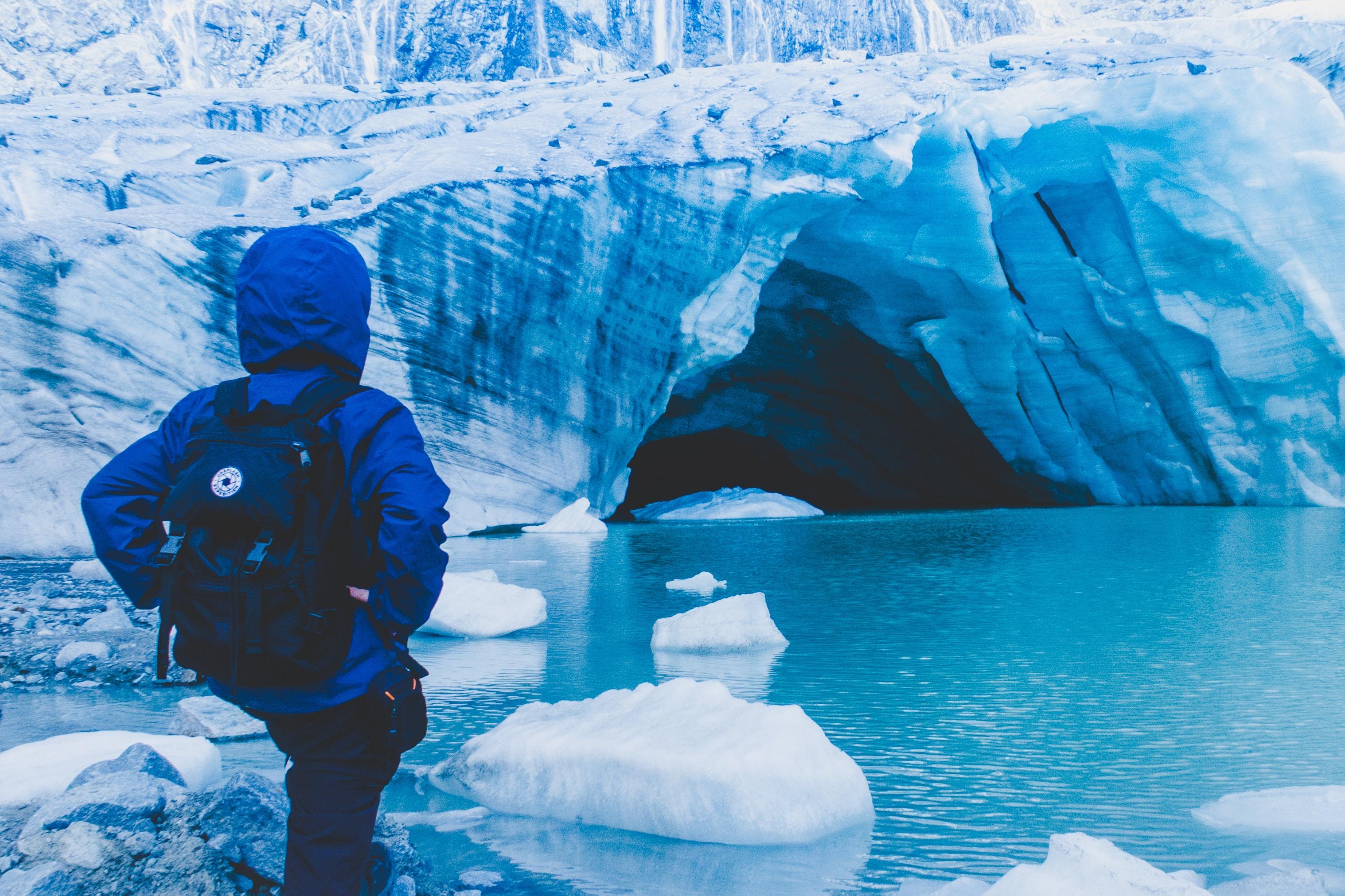 person wearing blue jacket standing near body of water