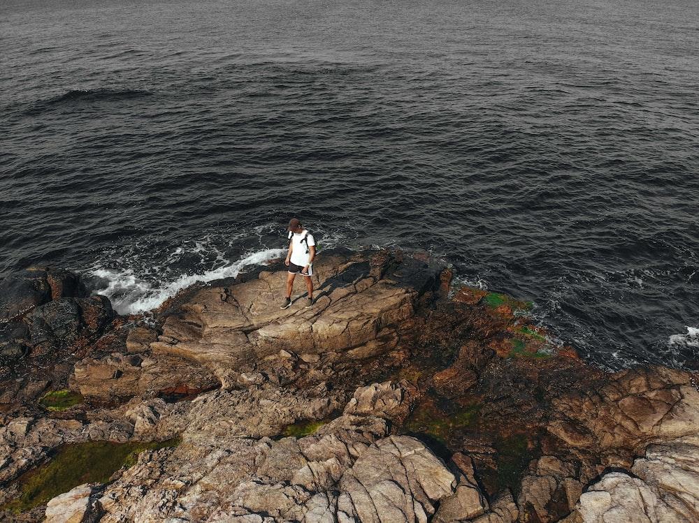 person standing on rocky seashore
