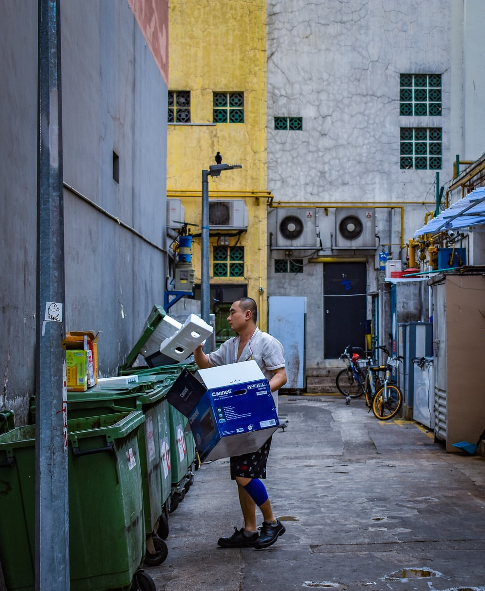 man in gray button-up shirt holding blue box near green garbage bin