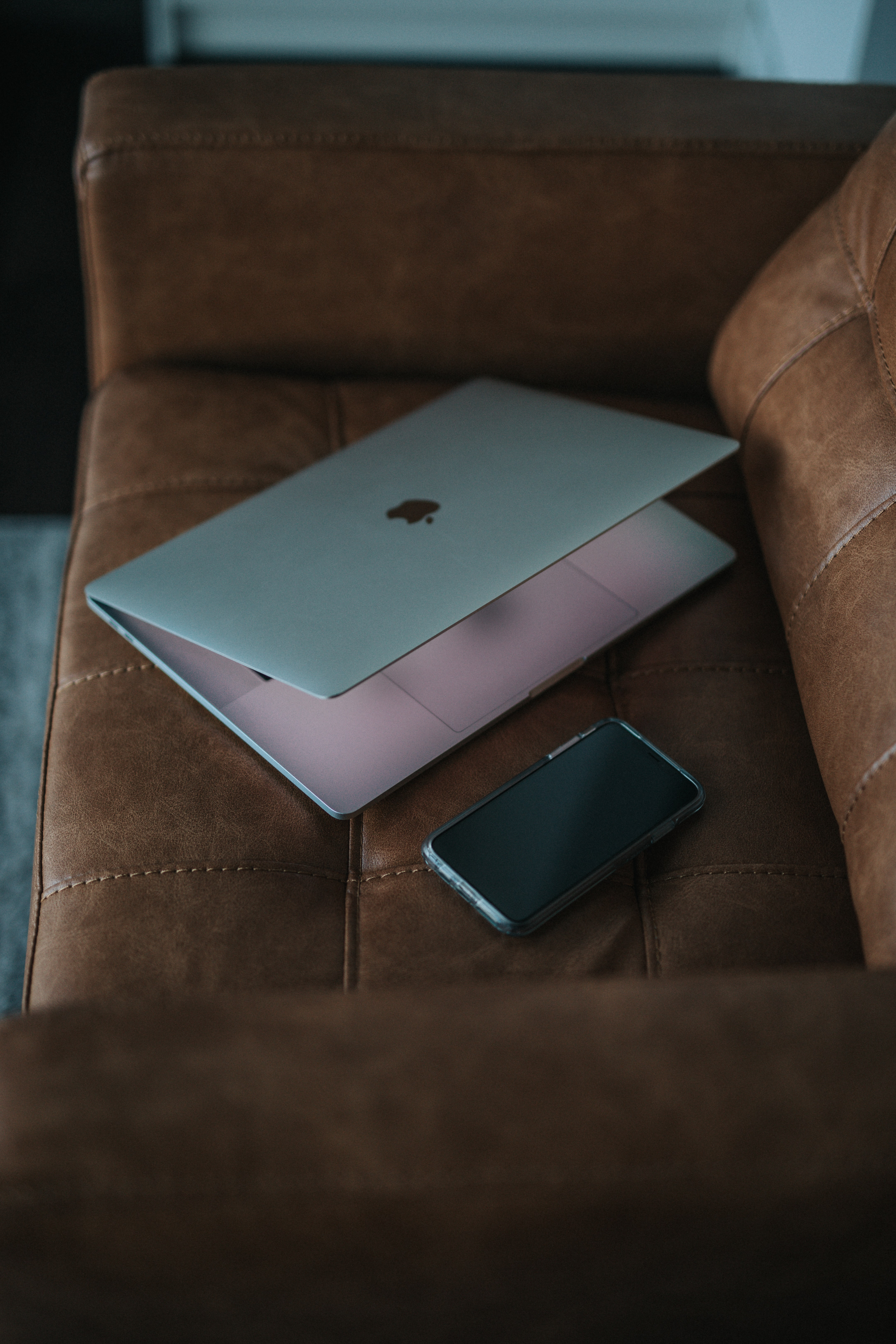 silver MacBook on sofa
