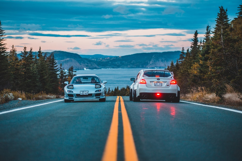 two silver car and hatchback on road during sunset