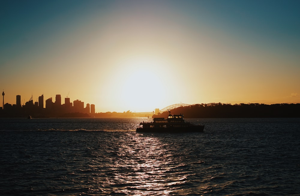 silhouette photography of boat sailing near city