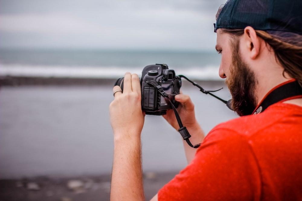 man holding DSLR camera taking photo