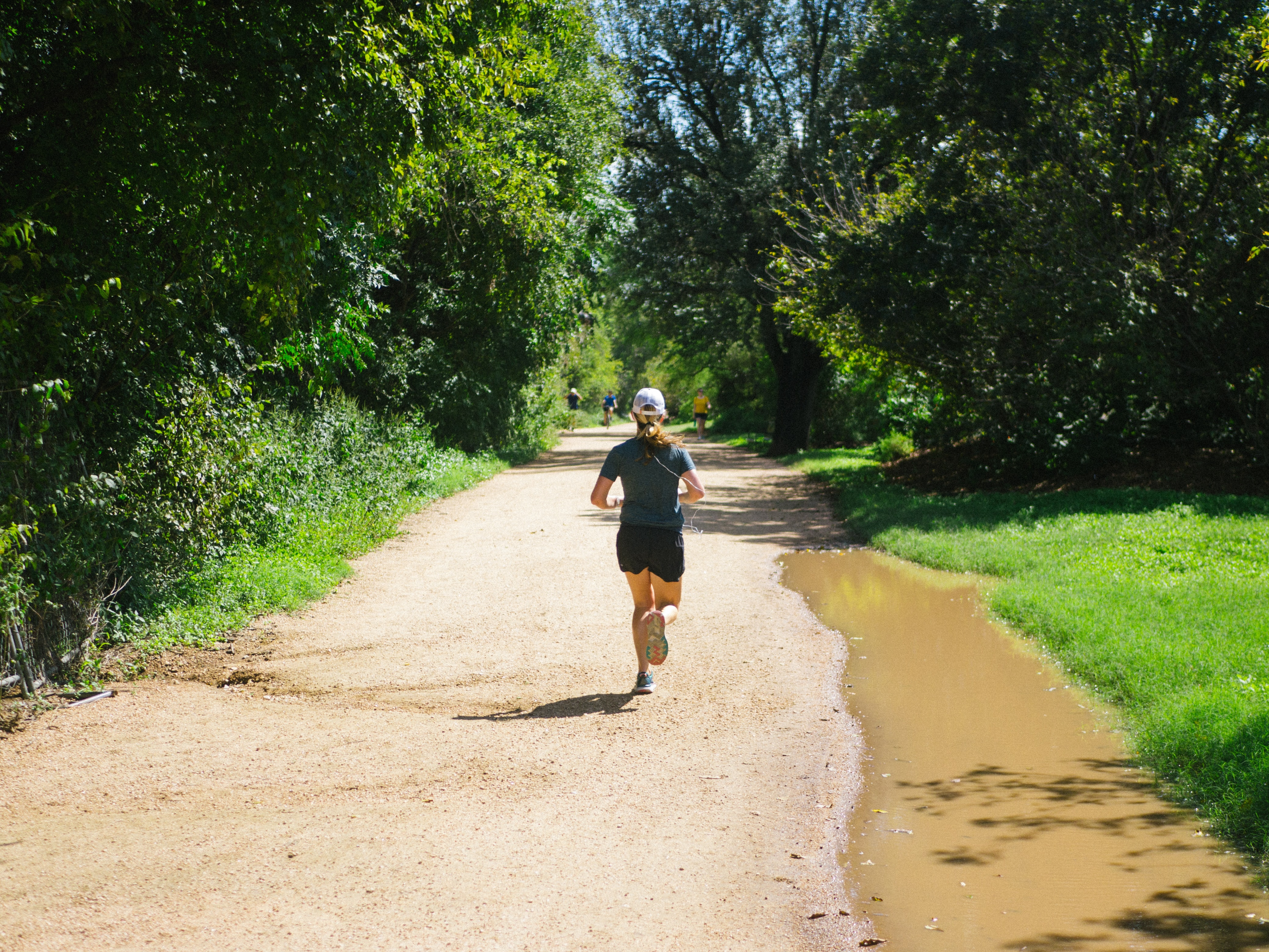 woman in blue shirt running on dirt pathway