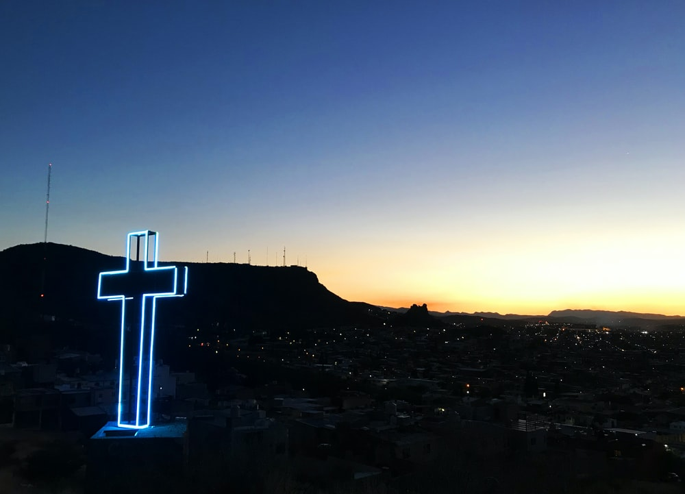 blue lighted cross decor during sunrise