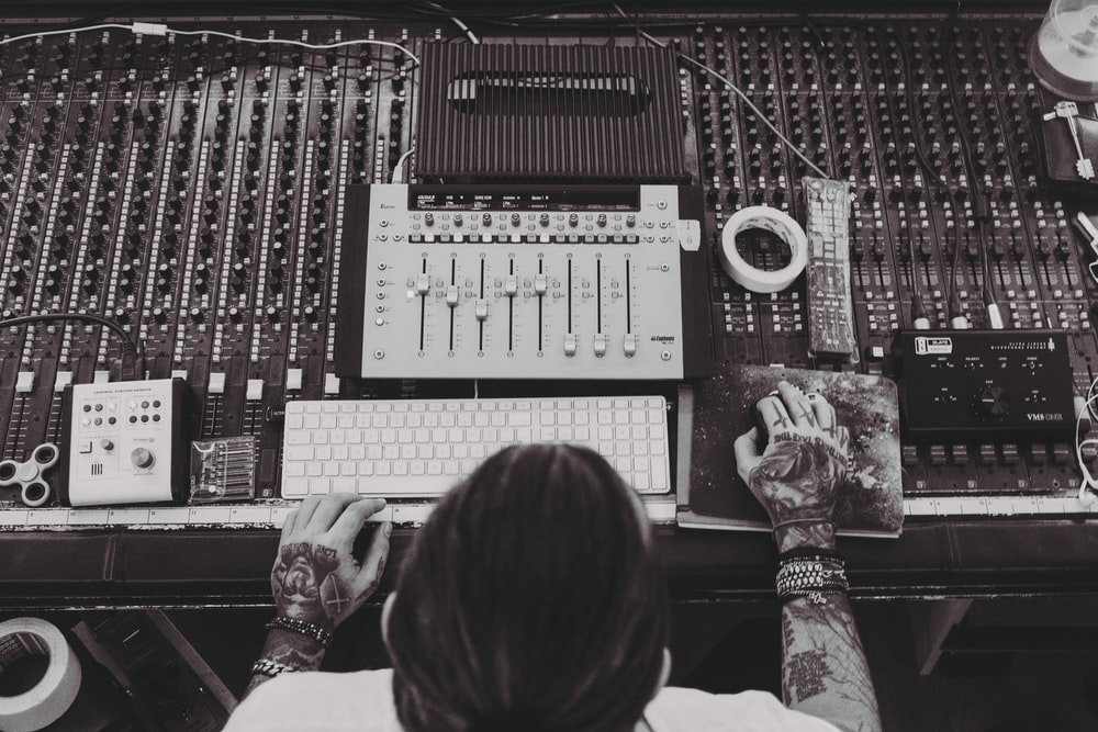 person controlling the audio mixer panel