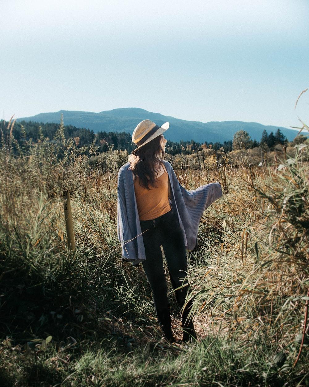 woman walking in grass fields