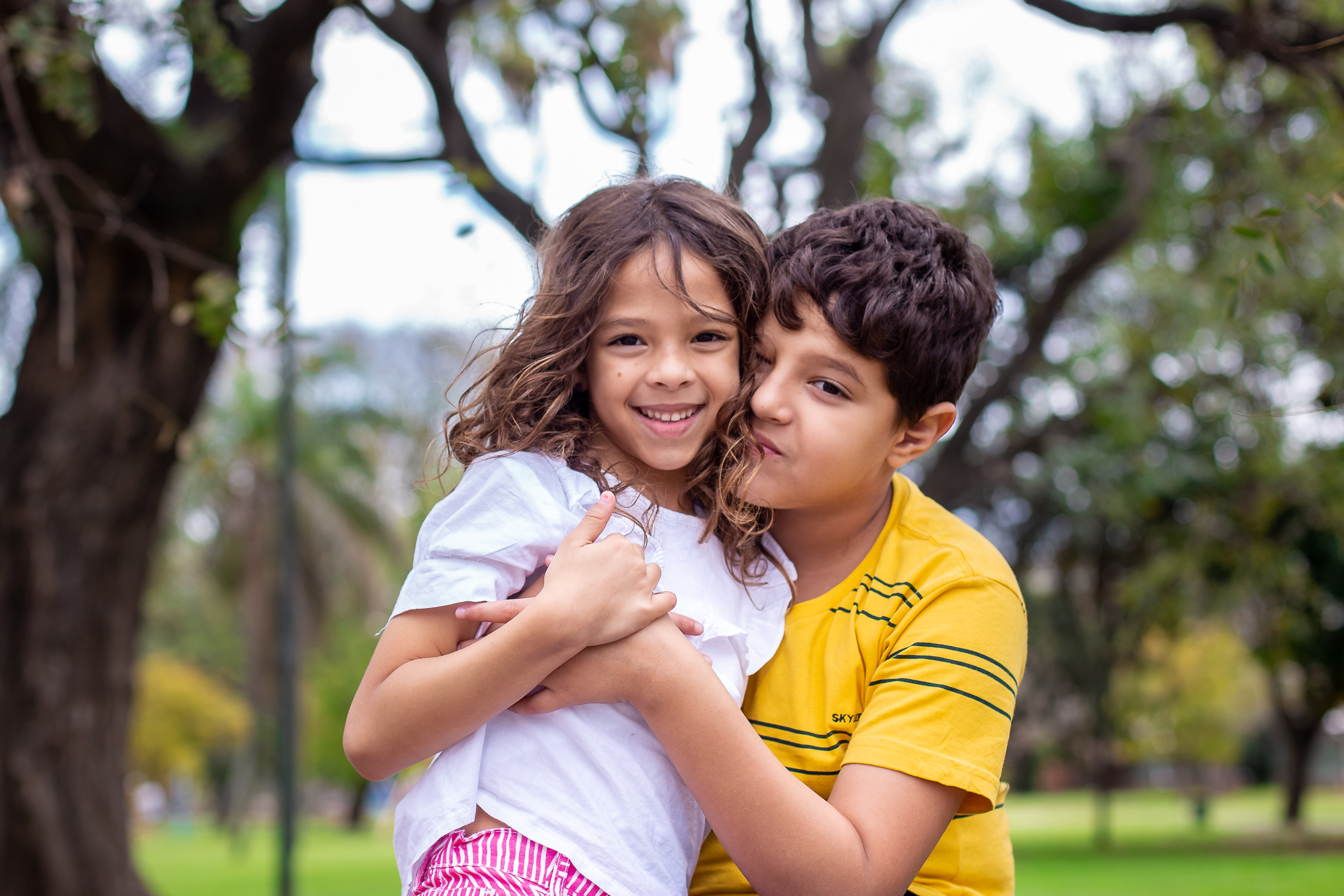 selective focus photography of boy hugging sister