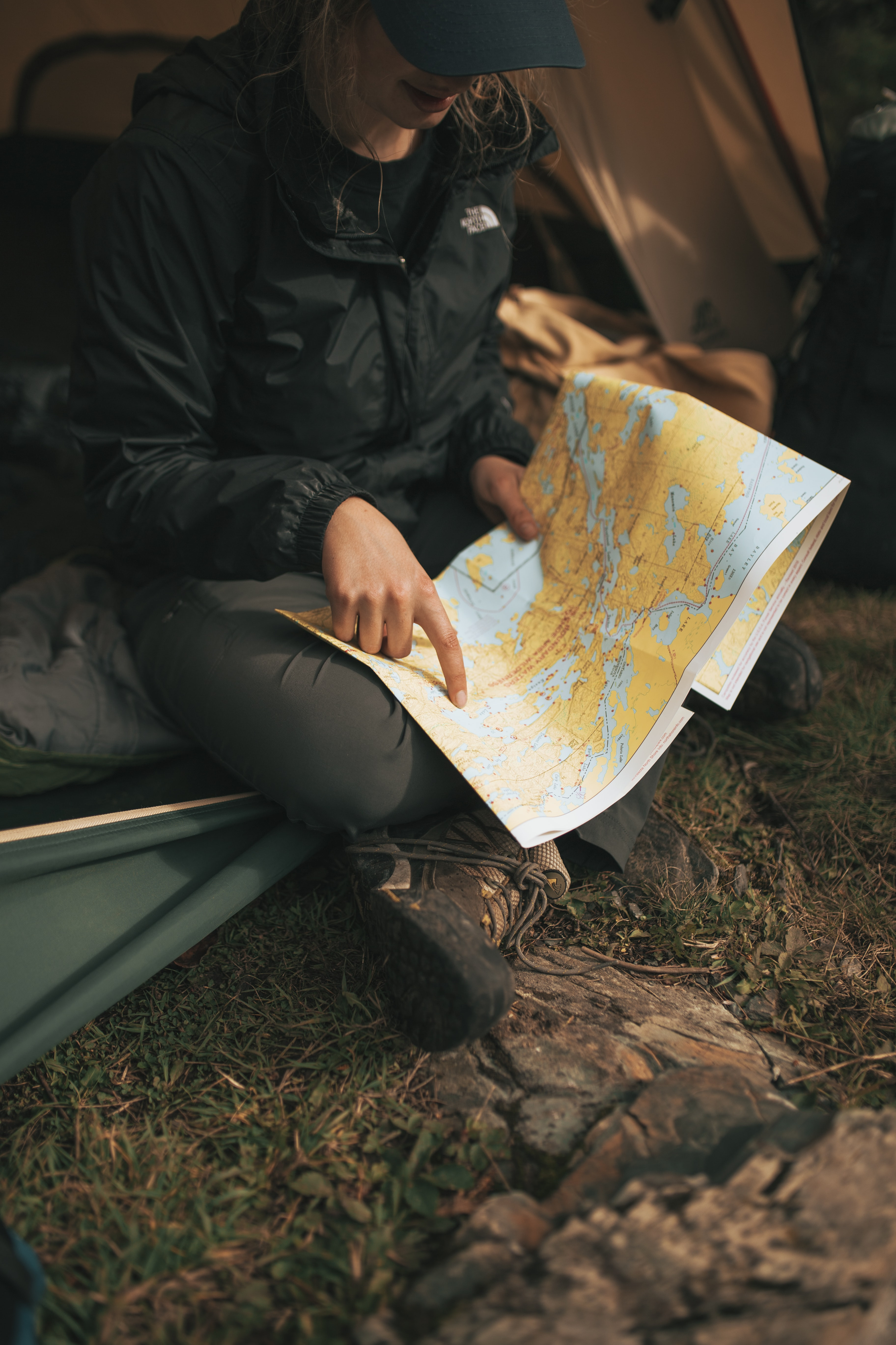 person wearing The North Face jacket sitting on sofa while holding map
