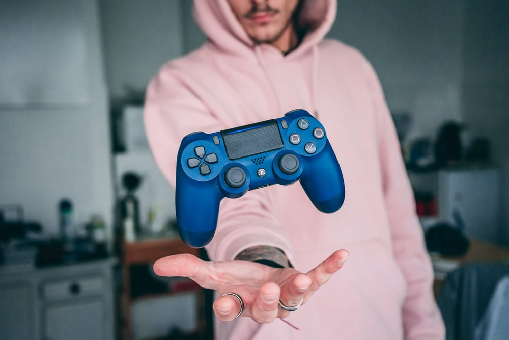 person holding blue Sony PS4 Dualshock 4 c
