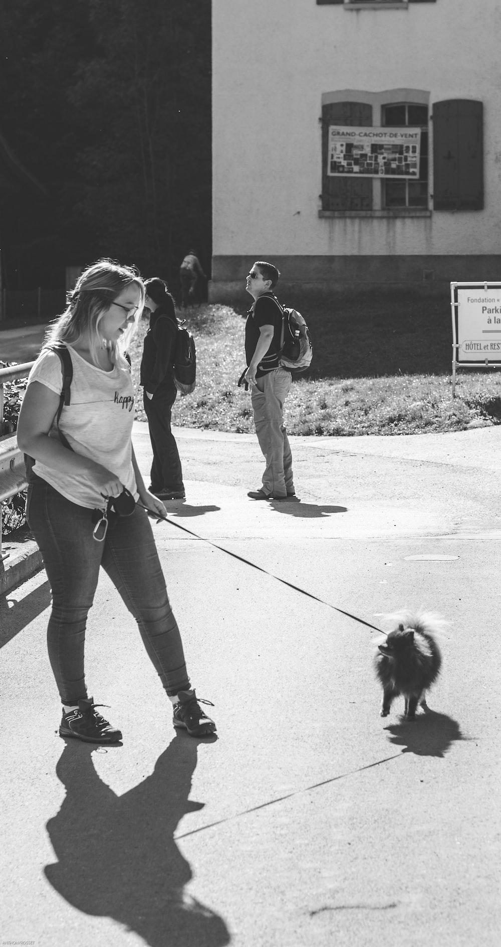 greyscale photo of woman walking the dog