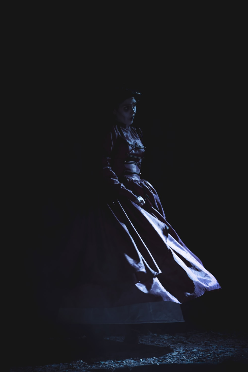 woman wearing gown sitting on chair inside dark room