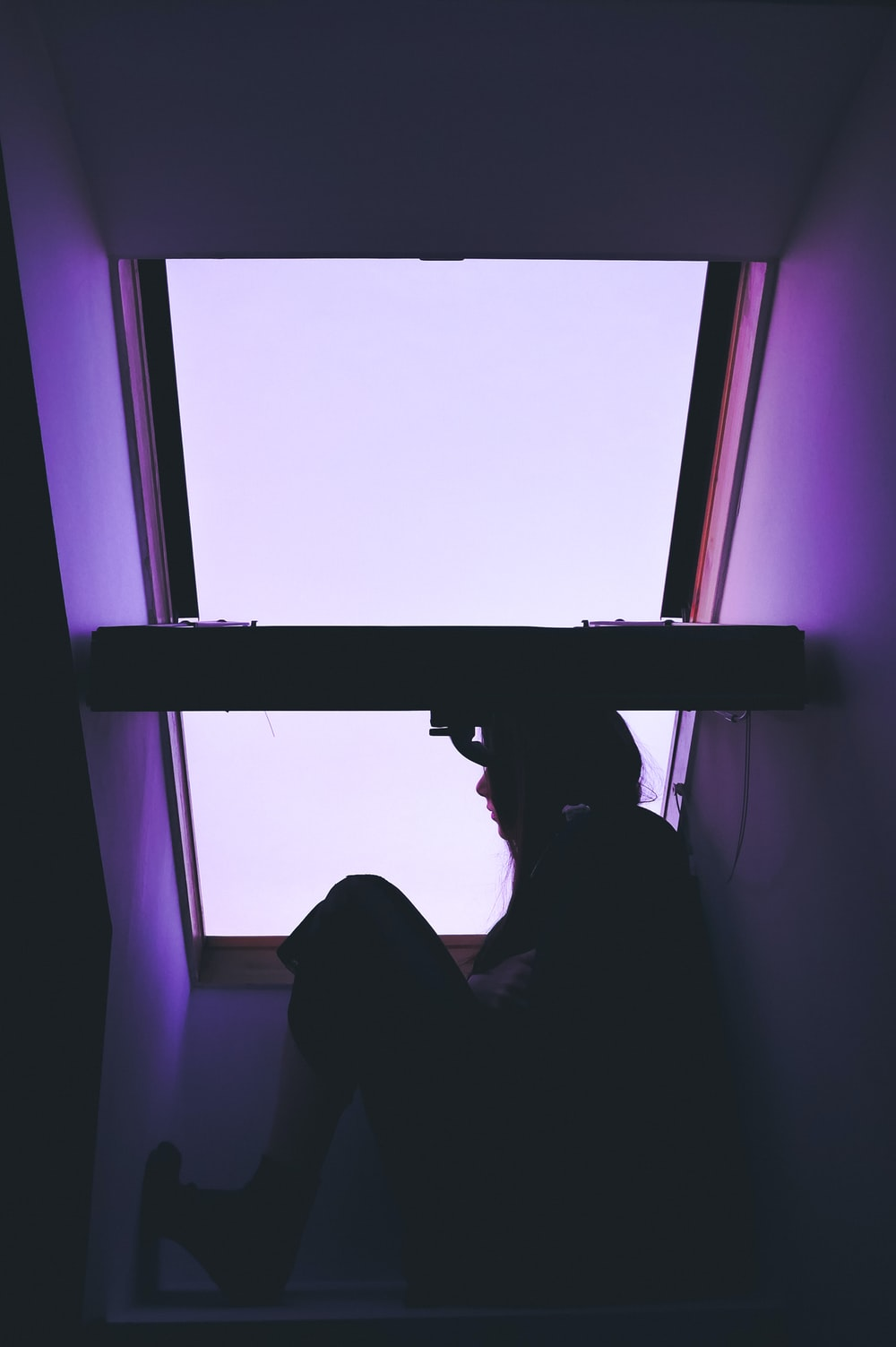 silhouette of person sitting near window