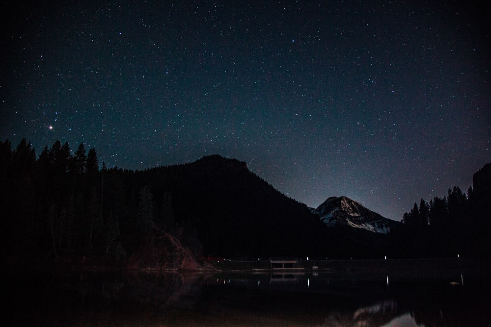silhouette of mountain near body of water during night