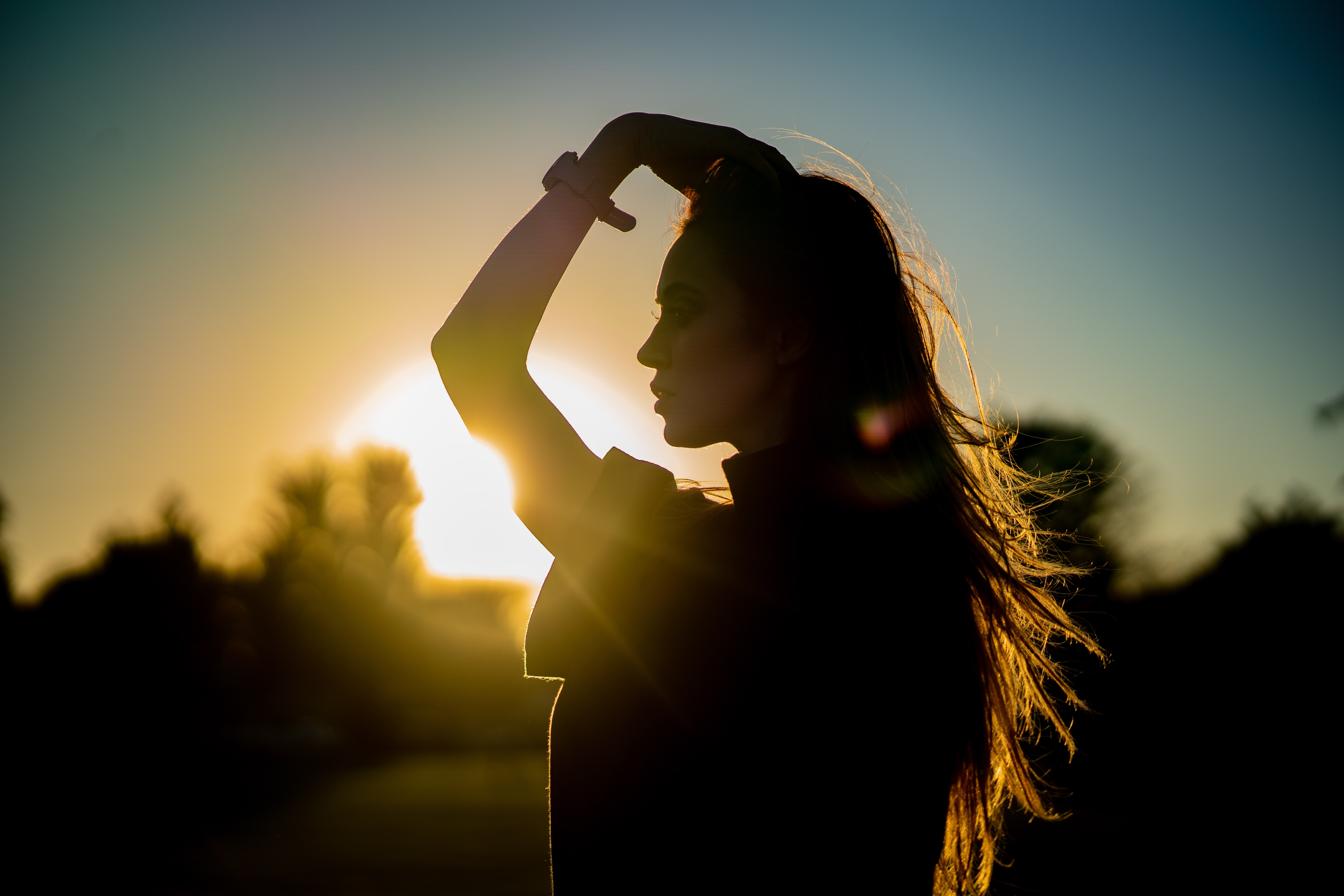 silhouette of woman with hangs on head during golden hour