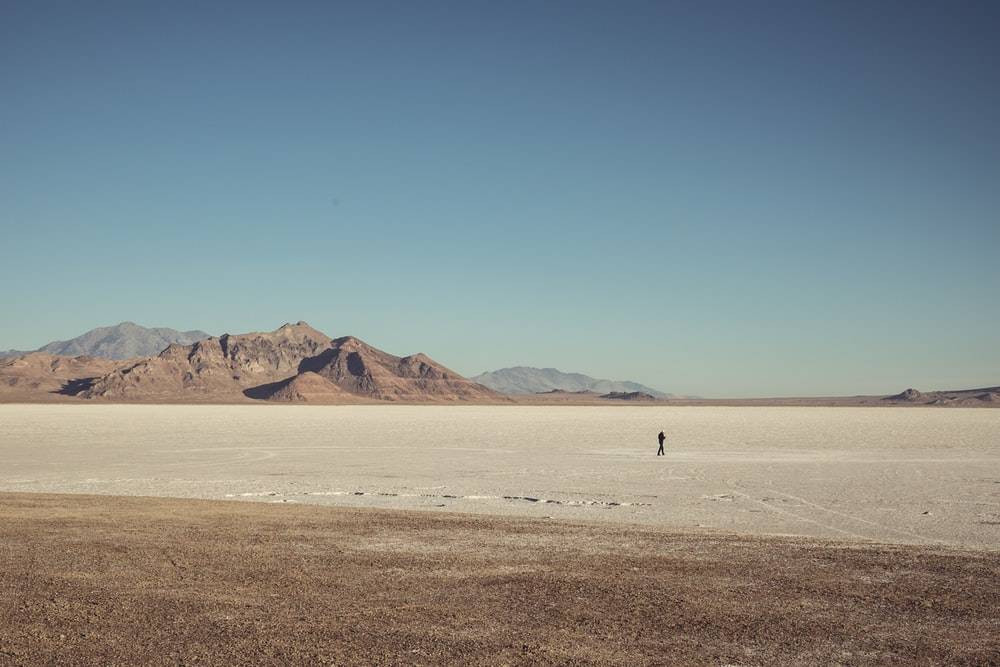 man walking in the middle of dessert