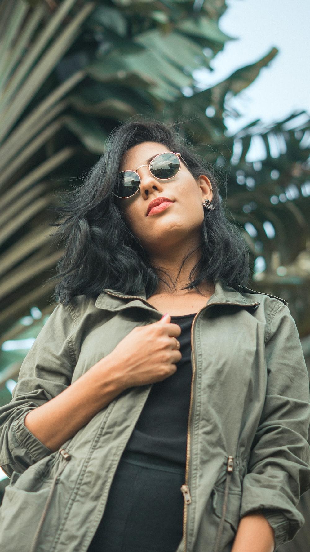 woman in grey zip-up jacket near palm tree