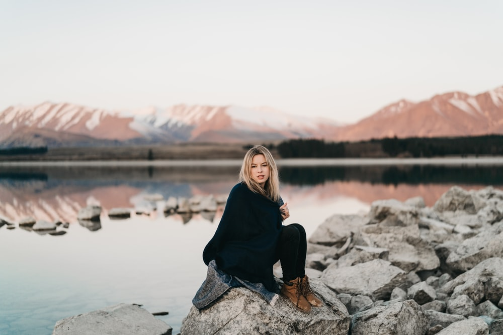 woman in black sitting on rock near lake