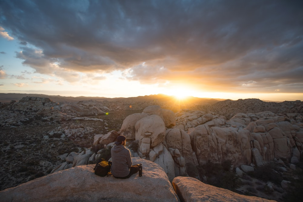 person sitting on rock formation and facing sunset
