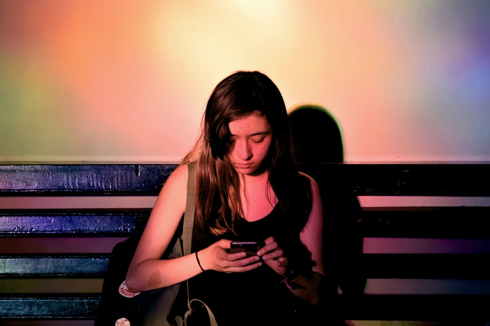 woman wearing black tank dress using smartphone