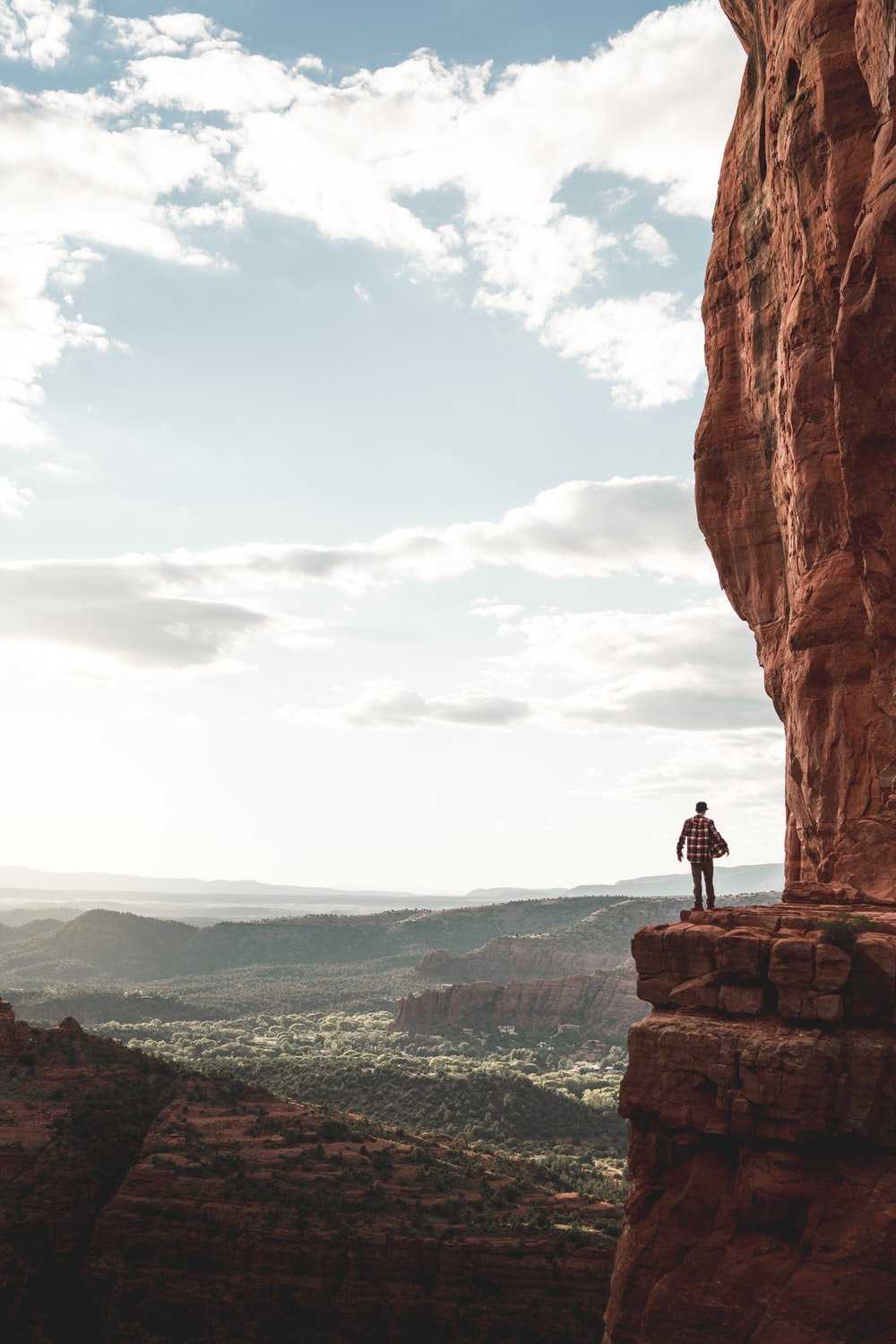 man standing on cliff during cloudy day