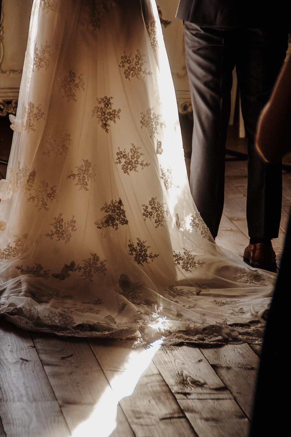 person wearing white lace floral wedding dress standing on brown wooden floor