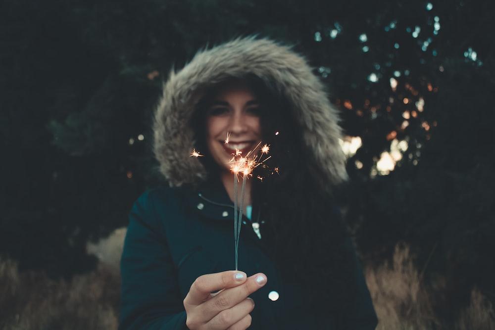 woman in fur-trim coat holding sparkler