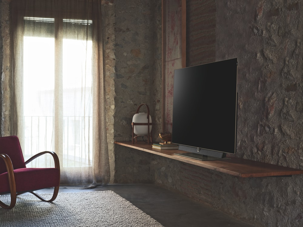 turned-off flat screen television on brown wooden TV stand