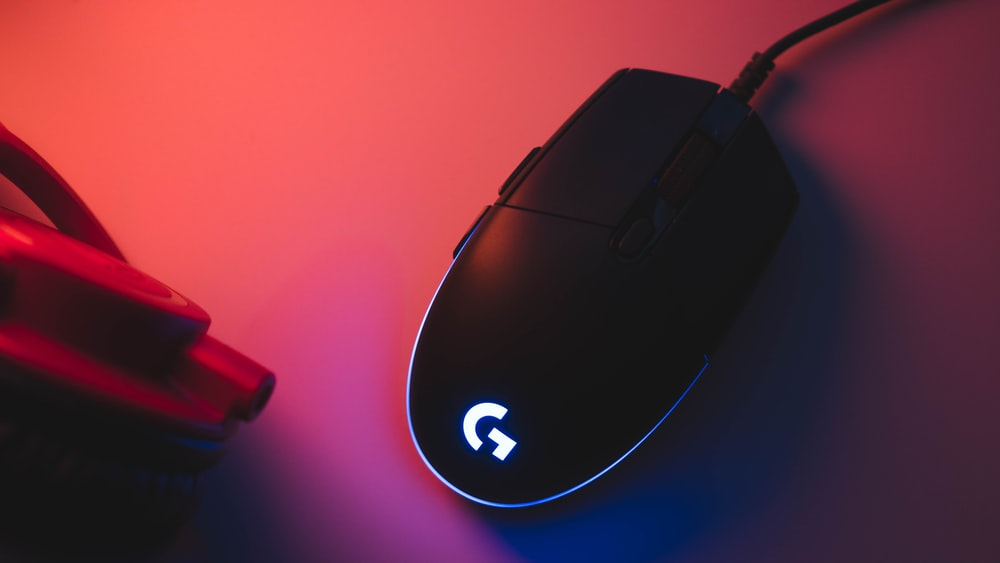 black Logitech G-series gaming mouse on red surface