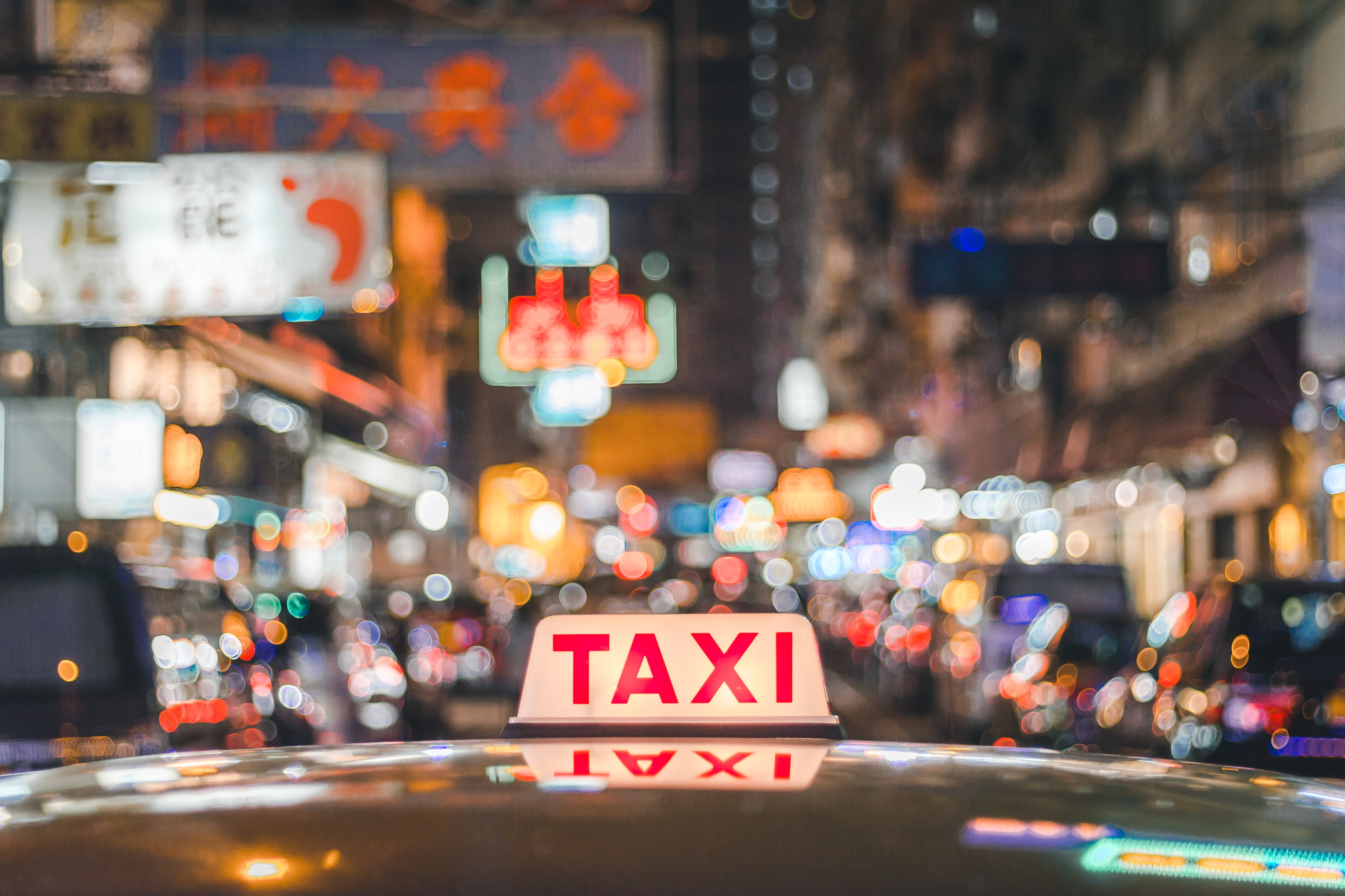 selective focus photo of red and white Taxi sign