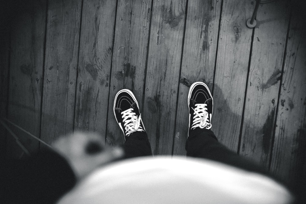 grayscale photo of person wearing Vans shoes